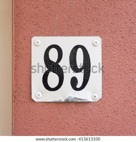 House number eighty nine on a pink plastered wall