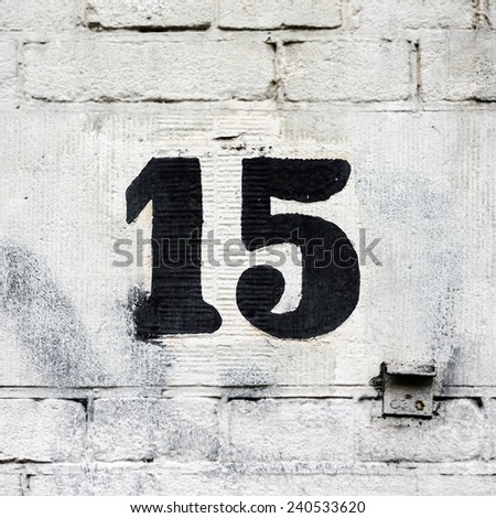 house number fifteen hand painted on a brick wall - stock photo