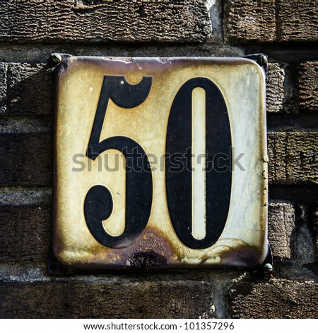 house number fifty on a rusted enameled plate
