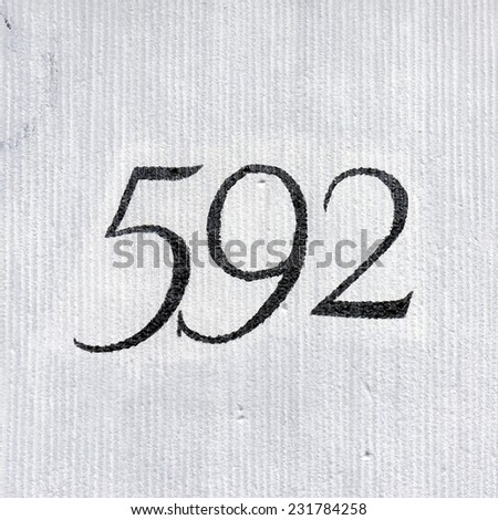House number five hundred and ninety two. Black numerals on a light background - stock photo