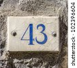 house number forty-three on a ceramic tile. - stock photo