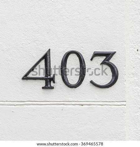 House number four hundred and three. Three separate numbers on a wall - stock photo