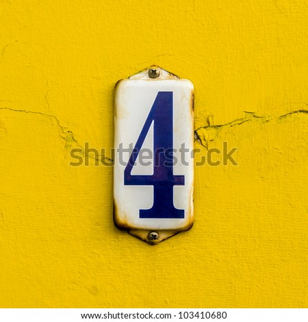 house number four on a rusty enameled plate against a bright yellow painted wall - stock photo
