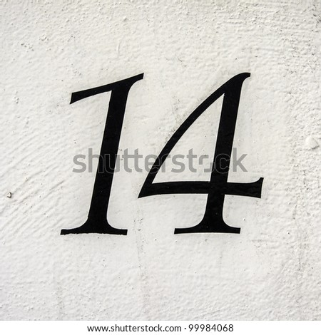 house number 14 on a white painted wall - stock photo