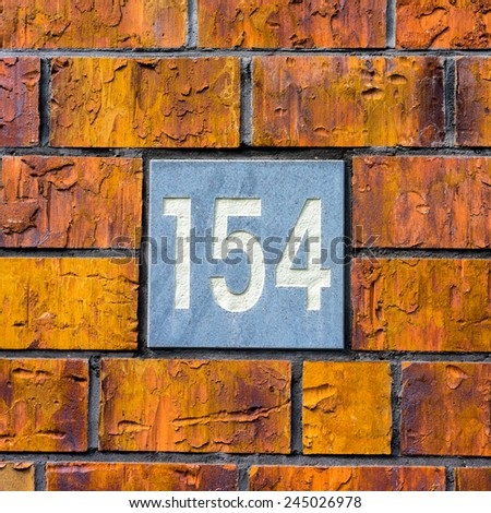 house number one hundred and fifty four, engraved in natural stone. - stock photo