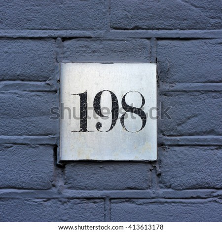 House number one hundred and ninety eight on a square aluminum plate. - stock photo