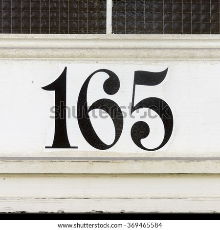 House number one hundred and sixty five. Black numerals on a white background. - stock photo