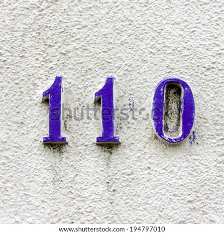 house number one hundred and ten. Blue relief lettering. - stock photo