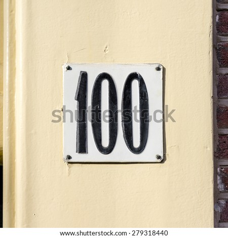 house number one hundred, embossed in a metal plate. - stock photo