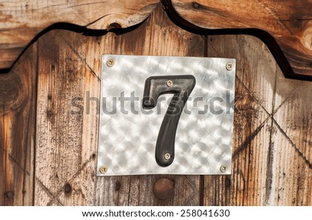 House number seven on pine wood - stock photo