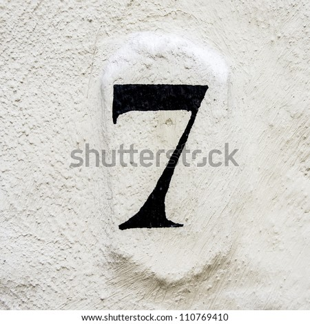 house number seven painted on a white plastered wall - stock photo