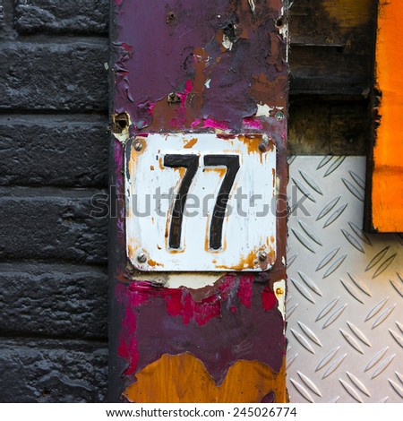 house number seventy seven, embossed in a metal plate - stock photo