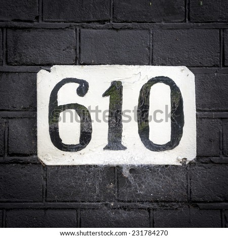 house number six hundred and ten painted on a white plate - stock photo