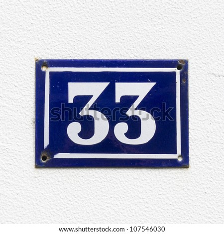 house number thirty-three, white lettering on a blue enameled plate - stock photo