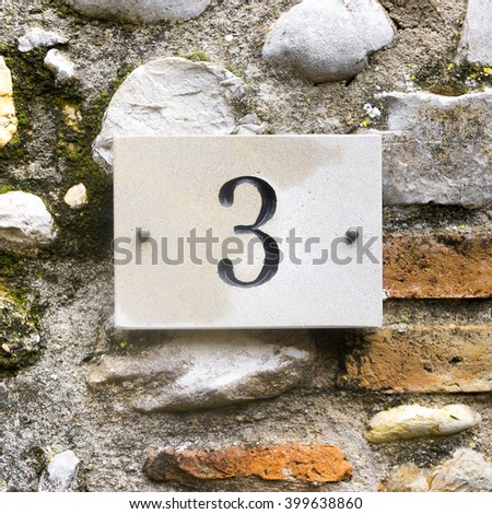 house number three engraved in natural stone - stock photo