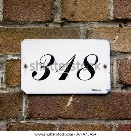 House number three hundred and eighteen. Black lettering on a white background. - stock photo