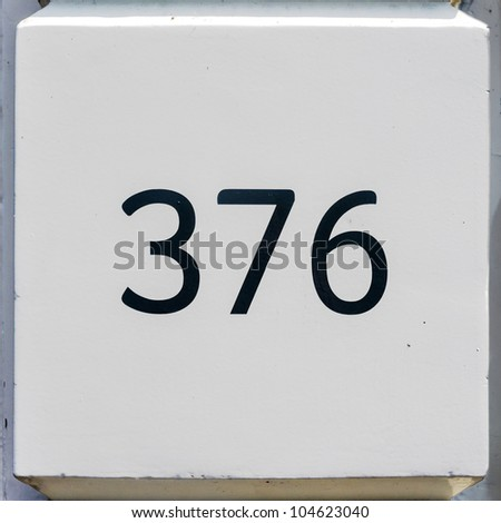 house number three hundred and seventy-six on a white wall segment - stock photo