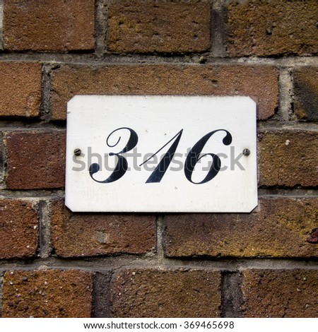 House number three hundred and sixteen. Black lettering on a white background. - stock photo