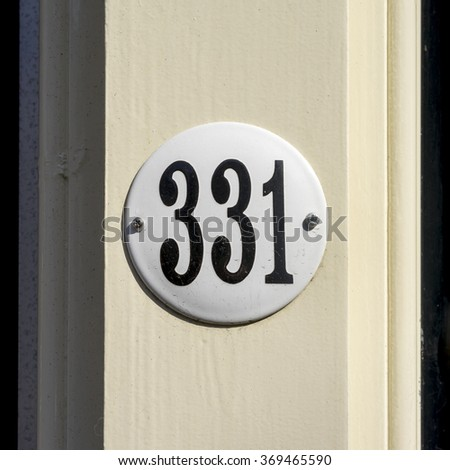 house number three hundred and thirty  one on a round enameled plate. - stock photo