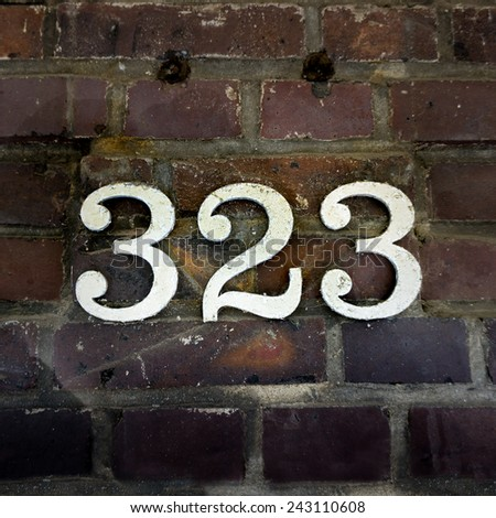 house number three hundred and twenty three. White numerals on a brick wall - stock photo