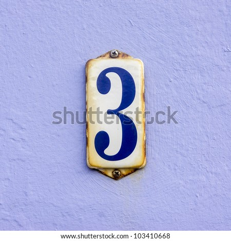 house number three on a rusty enameled plate against a light violet painted wall - stock photo