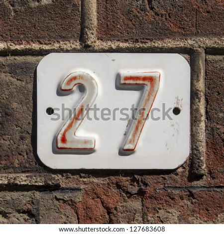 House number twenty seven. faded red lettering embossed in a  white metal plate - stock photo