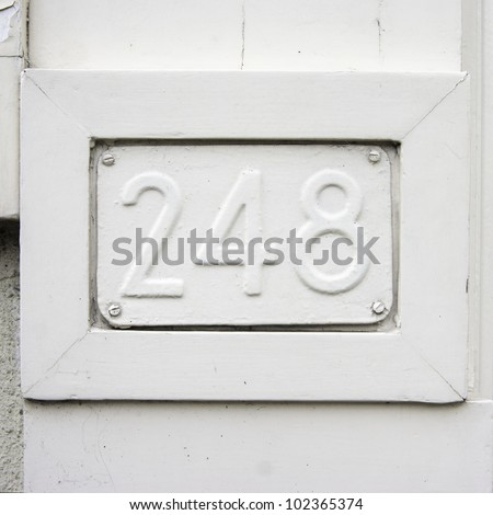 house number two hundred and forty-eight embossed in a metal placard. Over painted with white. - stock photo
