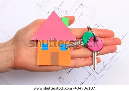 House of colored paper and home keys lying in hand of woman, electrical construction drawing of house in background, concept of building house