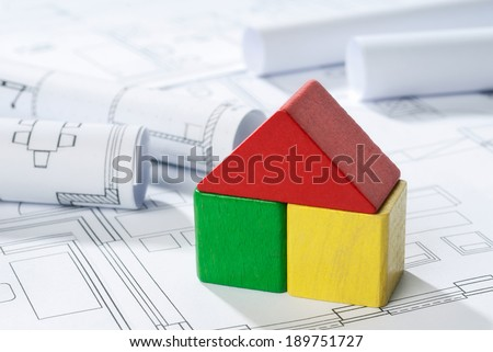 House of differently colored building blocks on blueprint.
