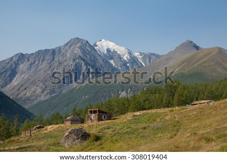 House of the shepherd and the mountains in the snow - stock photo