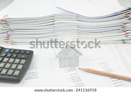 House on balance sheet and pencil with pile of paperwork as background. Stack of paperwork is high as work hard. Business and finance concepts rich and successful photography.
