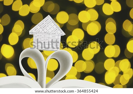 House on book as heart shape with defocused of glitter or golden bokeh circle at night as background. - stock photo