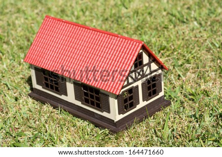 House on green grass. Concept photo of Real estate market bubble , rent, booming, money,price, grid, home, house, housing, industry and subprime mortgage crisis. (Copy Space) - stock photo