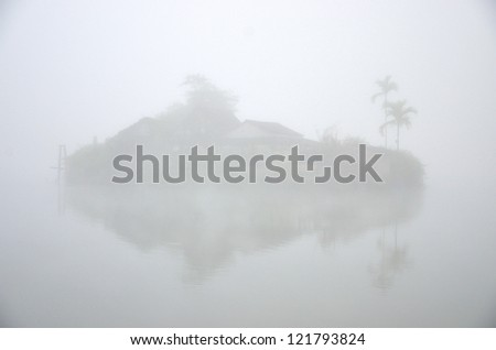House on island in the lake with foggy background