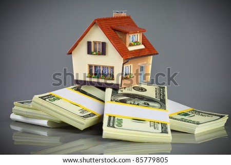 house on packs of banknotes on a grey background - stock photo