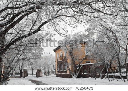 house on the snow-covered lane among trees