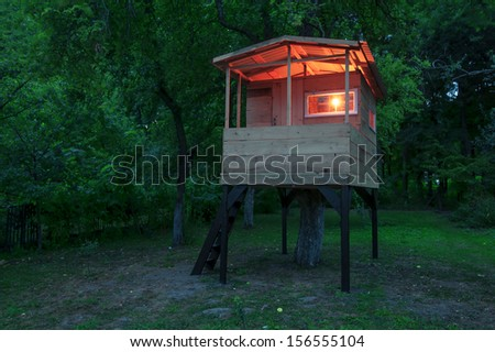 house on tree in evening garden - stock photo