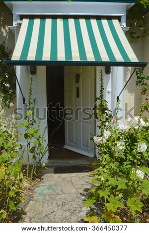 House open door with sun blind and Hollyhock flowers.