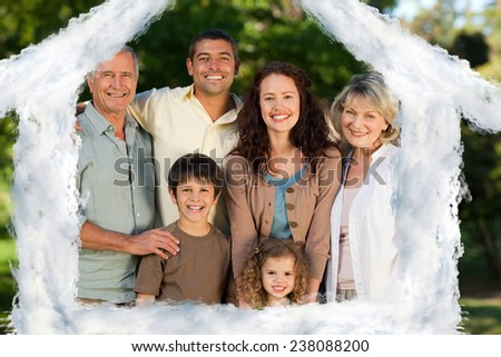 House outline in clouds against family looking at the camera in the park