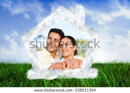 House outline in clouds against keyhole door in dark room - stock photo