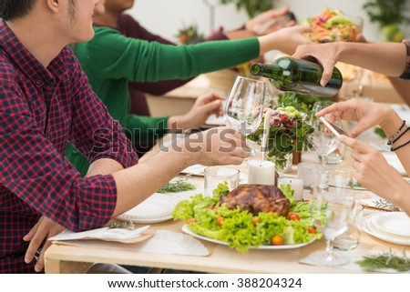 House owner drinking wine at party with his friends