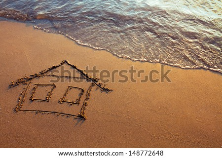 house painted on the beach, home on the sea - stock photo