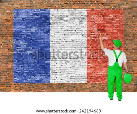 House painter covers old brick wall with flag of France - stock photo