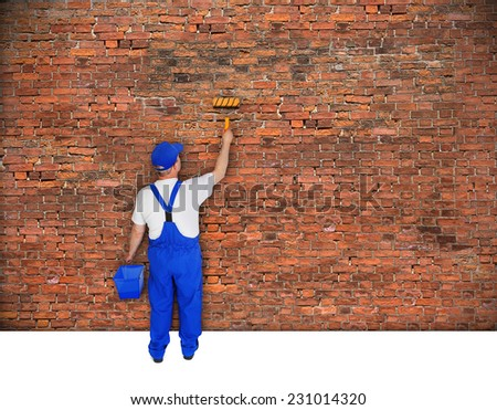house painter from behind paints brick wall  - stock photo