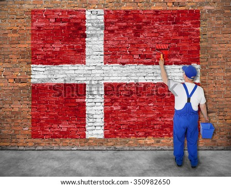 House painter paints flag of Denmark on old brick wall - stock photo