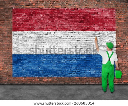 House painter paints flag of Hetherlands on old brick wall - stock photo