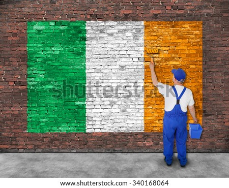House painter paints flag of Ireland on old brick wall, view from behind - stock photo