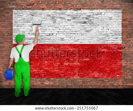 House painter paints flag of Poland on old brick wall