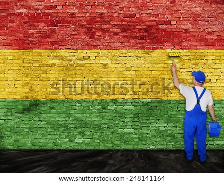 House painter paints flag of Reggae music on brick wall - stock photo
