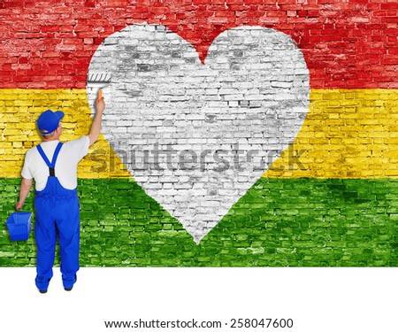 House painter paints heart symbol and flag of Reggae music. - stock photo